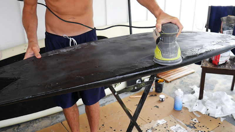 Sanding the surfboard