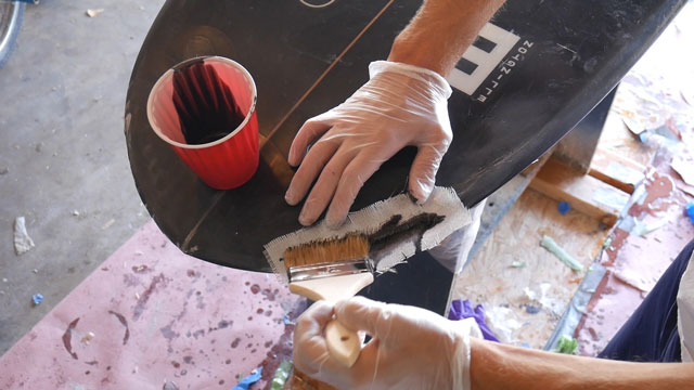 Applying resin to surfboard with paintbrush