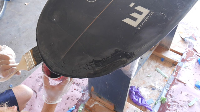Painting resin on surfboard