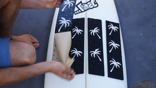 Peel the front pads and firmly push them onto surfboard