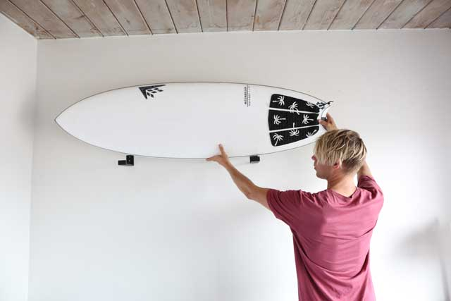 Hang surfboard on wall mounts