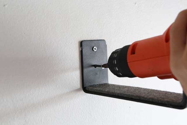 Tighten screws in wall rack
